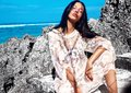 Woman model with dark long hair in transparent white long blouse dress posing near rocks Royalty Free Stock Photo