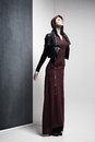 Woman model in long dress and leather jacket posing very dramatic in an minimal studio setup Royalty Free Stock Images