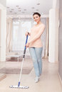 Woman mopping floor in living room having fun good looking young lady washes delicately with blue mop standing on her toes Stock Photography