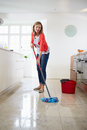 Woman mopping kitchen floor vertical image of a Royalty Free Stock Photo