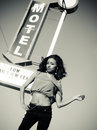 Woman beside motel street sign beautiful young standing retro vintage Royalty Free Stock Photos