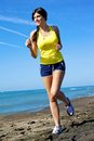 Woman in motion on the beach smiling happy running Royalty Free Stock Photos