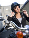 Young Woman on motorcycle adjusts helmet Royalty Free Stock Photo