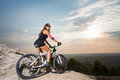 Woman with the mountain bike under a sky at sunset Royalty Free Stock Photo