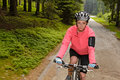 Woman mountain biking through forest road
