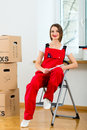 Woman with moving box in her house young women overall renovated the apartment because she moved to their new or old home Royalty Free Stock Image