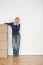 Woman with moving boxes on the phone a happy young standing in an empty room and having a conversation Stock Image