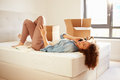 Woman moving into new home talking on mobile phone in bedroom lying down Stock Images