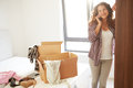 Woman moving into new home talking on mobile phone leaning against wardrobe Royalty Free Stock Photography