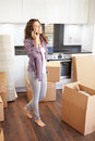 Woman moving into new home talking on mobile phone looking up Royalty Free Stock Photos