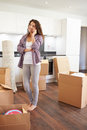 Woman moving into new home talking on mobile phone standing still Royalty Free Stock Image
