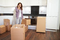 Woman moving into new home talking on mobile phone surrounded by boxes Royalty Free Stock Image