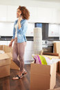 Woman moving into new home talking on mobile phone vertical image of a Royalty Free Stock Photography