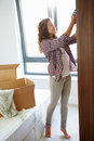 Woman moving into new home and unpacking boxes in bedroom putting clothes wardrobe Stock Photos