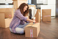 Woman moving into new home and unpacking boxes on her own Stock Photos