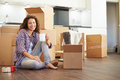 Woman moving into new home and unpacking boxes holding cup of coffee smiling at camera Royalty Free Stock Photos