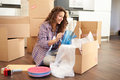 Woman moving into new home and unpacking boxes holding object Royalty Free Stock Image