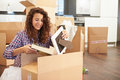 Woman moving into new home and unpacking boxes looking at picture frame book Stock Photos