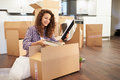 Woman moving into new home and unpacking boxes sitting on floor Stock Photo