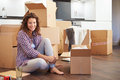 Woman moving into new home and unpacking boxes sitting on the floor smiling to camera Stock Photo