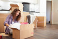 Woman moving into new home and unpacking boxes whilst sitting on the floor Royalty Free Stock Images