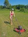 Woman mowing grass young in the yard Royalty Free Stock Photo