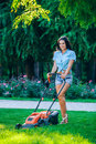 Woman mowing lawn in residential back garden Royalty Free Stock Photo