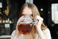 Woman with mug of alcohol beer at the cafe Stock Photos