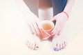 Woman with a mug of tea between s legs toes Royalty Free Stock Image