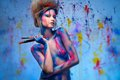 Woman muse with body art young creative and hairdo holding paint brushes Royalty Free Stock Image