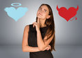 Woman musing between angel and devil hearts on gray background Royalty Free Stock Photo
