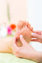 Woman in nail salon receiving foot massage a a pedicure by a beautician she is getting a Stock Photo