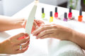 Woman in nail salon receiving manicure Royalty Free Stock Images