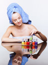 Woman with nail varnish young pretty spa in blue bath towel on head over mirror table on white background Stock Photography