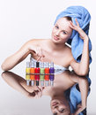 Woman with nail varnish young pretty spa in blue bath towel on head over mirror table on white background Stock Images