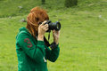 Woman nature photographer portrait of taking landscape pictures in the mountain area altai russia with green blurred meadow as a Stock Photo