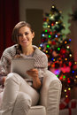 Woman near Christmas tree holding tablet PC Stock Image
