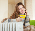 Woman near oil heater in home smiling with yellow cup at Stock Photo