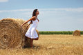 Woman near a rolled haystack gorgeous young standing and leaning on it Stock Photos