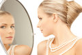 Woman with necklace from pearls and looking into the mirror Royalty Free Stock Photos
