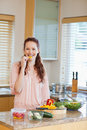 Woman nibbling bell pepper while preparing healthy salad Stock Photography