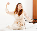 Woman in nightshirt awaking at home on white sheet bed Royalty Free Stock Photos