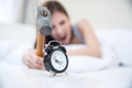 Woman not wanting to get up taking a hammer her alarm clock focus on clock Royalty Free Stock Image