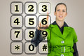 Woman with a numeric keypad on virtual interface raising her finger to activate numeral on the touchscreen Stock Images
