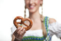 Woman offering a pretzel to the viewer in traditional dirndl which is hard baked brittle german biscuit in form of knot Royalty Free Stock Photo