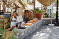 Woman offering products at street cafe in Paleochora town on Crete island Royalty Free Stock Photo