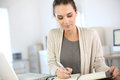Woman in office businesswoman writing on agenda Royalty Free Stock Image
