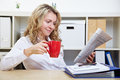 Woman in office reading newspaper Royalty Free Stock Photo