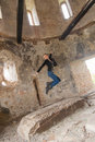 Woman at the old building jumping young blond into air in with ruined walls Stock Photos
