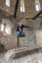 Woman at the old building jumping young blond into air in with ruined walls Royalty Free Stock Photography